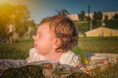 Das Kind liegt auf dem Gras lizenzfreie stockbilder