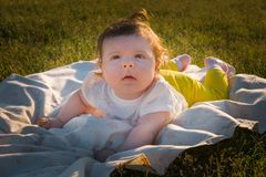 Das Kind liegt auf dem Gras stockfotografie