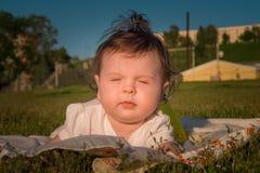 Das Kind liegt auf dem Gras stockbild