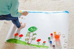 Das Kind malt die Wiese und die Bäume auf dem Papier und sitzt auf dem f Stockbild