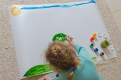 Das Kind malt die Wiese und die Bäume auf dem Papier und sitzt auf dem f Stockfotografie