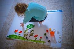 Das Kind malt die Wiese und die Bäume auf dem Papier und sitzt auf dem f Stockbilder