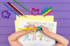 Das Kind malt eine Skizze der Familie Lizenzfreie Stockfotos