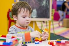 Das Kind montiert den Entwerfer Kindertätigkeit im Kindergarten oder zu Hause Kinderspiele mit einem Kind-` s Designer lizenzfreies stockfoto