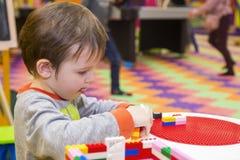 Das Kind montiert den Entwerfer Kindertätigkeit im Kindergarten oder zu Hause Kinderspiele mit einem Kind-` s Designer lizenzfreie stockbilder
