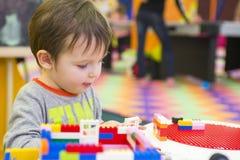 Das Kind montiert den Entwerfer Kindertätigkeit im Kindergarten oder zu Hause Kinderspiele mit einem Kind-` s Designer stockfotografie