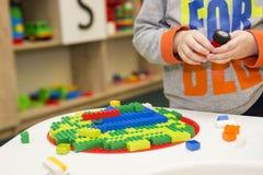 Das Kind montiert den Entwerfer Kindertätigkeit im Kindergarten oder zu Hause Kinderspiele mit einem Kind-` s Designer lizenzfreie stockfotografie