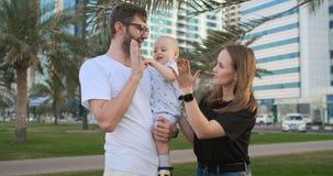 Das Kind nimmt die Palme der lächelnden und lachenden Stellung des Vaters im Sommerpark stock footage