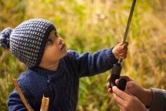 Das Kind nimmt einen Regenschirm von den Händen des Elternteils lizenzfreies stockbild