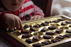 das Kind nimmt Süßigkeit das Kind isst Süßigkeit und wünscht mehr stockbilder