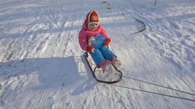 Das Kind reitet einen Schlitten Kinderspiel draußen im Schnee stock video footage