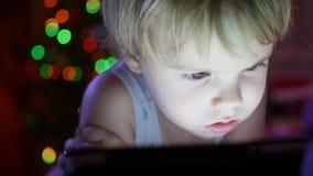 Das Kind schaut zur Tablette, die auf Bett liegt Im Hintergrund, in den Lichtern und in den Girlanden der Weihnachtstanne Stockfotografie