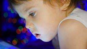 Das Kind schaut zur Tablette, die auf Bett liegt Im Hintergrund, in den Lichtern und in den Girlanden der Weihnachtstanne Stockfoto