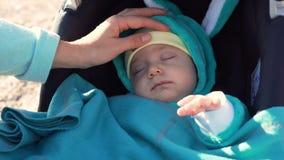 Das Kind schläft auf dem Strand Mutteranschläge sein Kopf stock footage