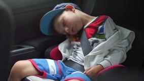 Das Kind schläft in einem Stuhl im Auto stock footage