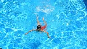 Das Kind schwimmt im blauen Wasser des Pools Ansicht von oben stock video footage