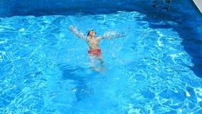 Das Kind schwimmt im blauen Wasser des Pools Ansicht von oben stock footage