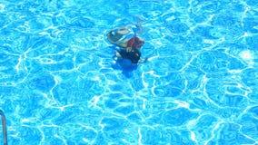 Das Kind schwimmt im blauen Wasser des Pools Ansicht von oben Das Mädchen taucht in das Wasser stock video footage