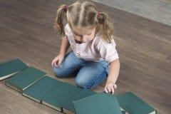 Das Kind sitzt auf dem Boden und ordnet Bücher neu Lizenzfreies Stockbild