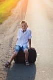 Das Kind sitzt auf einem Koffer am sonnigen Tag des Sommers Stockfoto