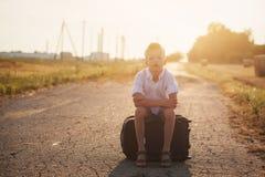 Das Kind sitzt auf einem Koffer am sonnigen Tag des Sommers, die Reise Lizenzfreie Stockfotos