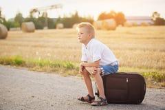 Das Kind sitzt auf einem Koffer am sonnigen Tag des Sommers, die Reise Lizenzfreie Stockfotografie