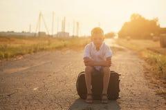 Das Kind sitzt auf einem Koffer am sonnigen Tag des Sommers, die Reise Lizenzfreie Stockbilder