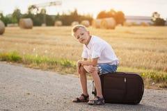 Das Kind sitzt auf einem Koffer am sonnigen Tag des Sommers, die Reise Lizenzfreies Stockbild