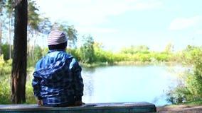 Das Kind sitzt auf einer Bank nahe dem See im Park Wege in der Frischluft stock video