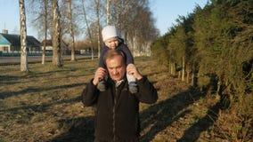 Das Kind sitzt auf seinem großväterlichen ` s Hals und sie gehen in den Park bei Sonnenuntergang Meine Enkelin mag einen Mann rei stock footage