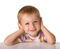 Das Kind sitzt an einem Tisch Stockfoto