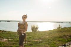 Das Kind sitzt im Riemen an der Mutter stockfotografie
