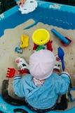 Das Kind sitzt im Sandkasten Lizenzfreies Stockfoto