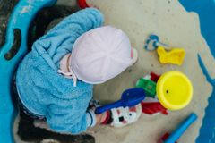 Das Kind sitzt im Sandkasten Lizenzfreie Stockfotos