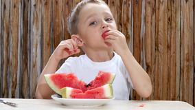 Das Kind sitzt am Tisch auf dem Hintergrund einer hölzernen Wand und mit Vergnügen isst eine Wassermelone stock footage