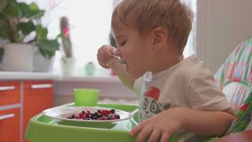 Das Kind sitzt am Tisch und isst einen Löffelvoll frische Beeren Nützliches und gesundes Lebensmittel Stockfotografie
