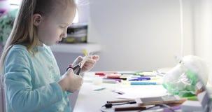 Das Kind sitzt am Tisch und macht Handwerk liebhaberei stock video footage