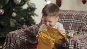 Das Kind sitzt unter dem Weihnachtsbaum und öffnet sein Geschenk stock video footage