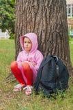 Das Kind sitzt unter einer großen Eiche Stockfotografie
