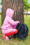 Das Kind sitzt unter einer großen Eiche Lizenzfreie Stockfotos