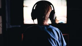 Das Kind sitzt vor dem Fernsehen und spielt ein Videospiel Hintere Ansicht K?hle Gesamtl?nge Sch?ne Leuchte stock footage