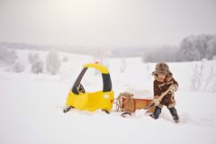 Das Kind spielt draußen im verschneiten Winter stockfotos