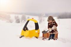 Das Kind spielt draußen im verschneiten Winter lizenzfreies stockfoto