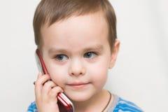 Das Kind spricht durch Telefon Stockbilder