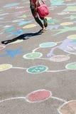 Das Kind springend auf die kindischen Zeichnungen auf dem Asphalt Lizenzfreies Stockbild