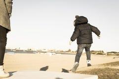 Das Kind springend in den Sand stockfotografie