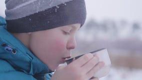 Das Kind trinkt Tee im Winter draußen im Park Lizenzfreies Stockbild