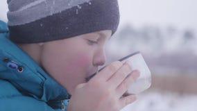 Das Kind trinkt Tee im Winter draußen im Park Stockfotos