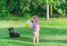 Das Kind und der Hund spielen in einem Gras Lizenzfreies Stockbild
