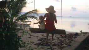 Das Kind und die Mutter, die auf ein Schwingen auf dem Strand reinigen stock video footage